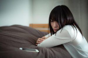 ベッドでうなだれる女性